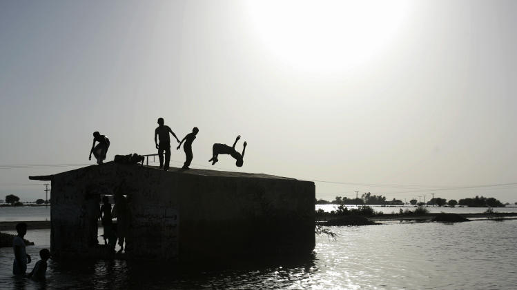 A Pakistani boy does a backflip from the roof of a house as he plays with other villagers in the floodwaters of Sehwan division, southern Pakistan on Tuesday Sept. 28, 2010. The floods have caused some 8 million people homeless in what Pakistani and U.N. officials have said is one of the largest humanitarian disasters in living memory.(AP Photo/Aaron Favila)