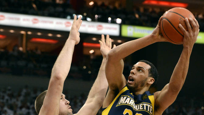 Marquette's Trent Lockett, left, shoots over the defense of Louisville's Stephan Van Treese during the first half of their NCAA college basketball game on Sunday, Feb. 3, 2013, in Louisville, Ky. (AP Photo/Timothy D. Easley)