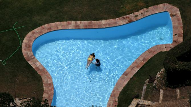 Women cool off at a swimming pool during the second heat wave of the summer, in Ronda
