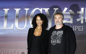 """French director Besson and his wife and producer Silla pose for photographs during a news conference for his movie """"Lucy"""" in Taipei"""