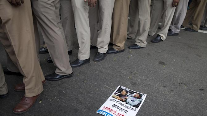 Indian policemen stand near a poster showing a photo of Indian External Affairs Minister, Sushma Swaraj, and former Indian Premier League chief, Lalit Modi, during a protest by supporters of India's Aam Aadmi Party (AAP), or Common Man's Party in New Delhi, India, Monday, June 29, 2015. The poster says 'helper of fugitive Lalit Modi, Sushma Swaraj, resign.'  Swaraj allegedly helped Modi procure travel documents after he fled the country fearing corruption charges. (AP Photo/Tsering Topgyal)