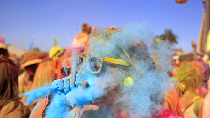 AP10ThingsToSee - A woman blows blue paint powder on to her friend during the Holi One colour festival in Cape Town, South Africa, Saturday, March 2, 2013. Thousands of people took part in the festival to express freedom and the colour of everyday life. (AP Photo/Schalk van Zuydam, File)