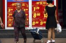 File picture of shoppers walking past and look at a board displaying food prices at a shopping mall in central Beijing