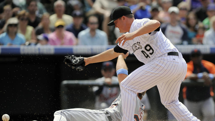 Detroit Tigers' Brennan Boesch scores as the ball is knocked from the glove of Colorado Rockies pitcher Rex Brothers on a wild pitch in the 7th inning of a baseball game in Denver on Sunday, June 19, 2011. Brothers left the game after the play with an injury to his arm. The Tigers won 9-1. (AP Photo/Chris Schneider)
