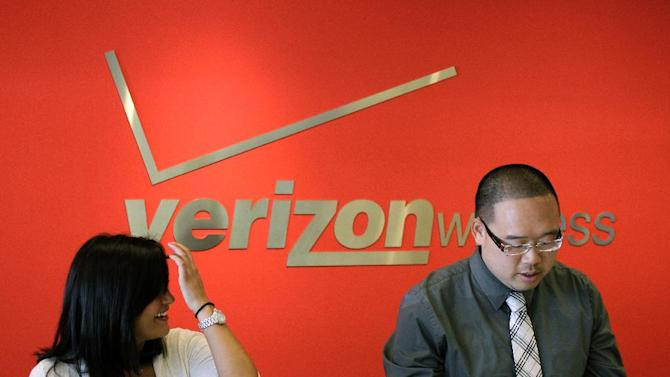 Two Verizon workers take orders at a Verizon store in Mountain View, Calif., Tuesday, June 12, 2012. Verizon Wireless, the nation's largest cellphone company, announced Tuesday  that is dropping nearly all of its phone plans in favor of pricing schemes that encourage consumers to connect their non-phone devices, like tablets and PCs, to Verizon's network. (AP Photo/Paul Sakuma)