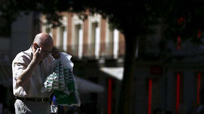 A man carries shopping bags of Spain's family-owned department store group El Corte Ingles as he adjusts his glasses in central Madrid