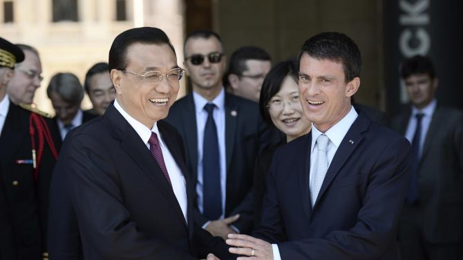 French Prime Minister Manuel Valls shakes hands with Chinese Premier Li Keqiang during a welcoming ceremony at the Hotel National des Invalides in Paris