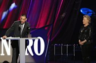 As Bette Midler looks on, right, Gil Bianchini accepts induction into the Rock and Roll Hall of Fame for his late mother, Laura Nyro, Saturday, April 14, 2012, in Cleveland. (AP Photo/Tony Dejak)