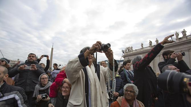 """People take pictures as they wait for Pope Francis in St. Peter's Square at the Vatican, Thursday, Dec. 25, 2014. Tens of thousands of Romans and tourists in St. Peter's Square listened as the pontiff delivered the Catholic church's traditional """"Urbi et Orbi"""" (Latin for """"to the city and to the world) Christmas message from the central balcony of St. Peter's Basilica. Francis said: """"truly there are so many tears this Christmas."""" (AP Photo/Alessandra Tarantino)"""