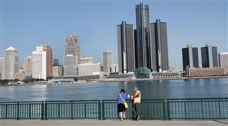 People stand at the Windsor river walk with the Detroit skyline behind them along the Detroit river in Windsor, Ontario
