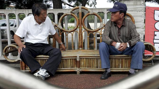 File photo of former North Koreans talking in front of the community center of Abaimaul near the port of Sokcho
