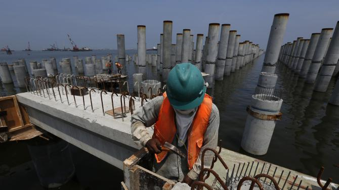 Workers toil at the construction site of a new pier at New Priok container terminal in north Jakarta
