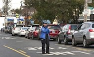 <p>A New York City police office directs gas station traffic as long lines form on City Island. Damage from the deadly superstorm that blasted the US East Coast and shut down New York City could hit $50 billion, economists said Thursday, but the impact on the broader economy will be minor.</p>