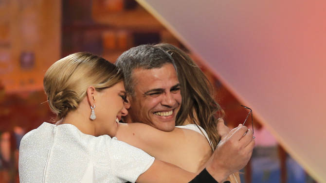 Director Abdellatif Kechiche, centre, is embraced by Lea Seydoux, left, and Adele Exarchopoulos after they were presented the Palme d'Or award for La Vie D'Adele during an awards ceremony at the 66th international film festival, in Cannes, southern France, Sunday, May 26, 2013. (AP Photo/Francois Mori)