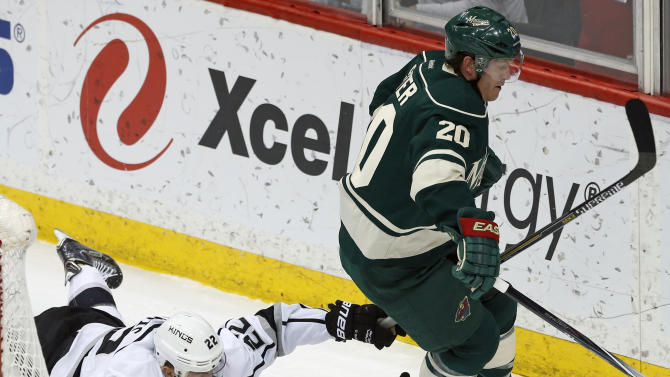 Los Angeles Kings' Trevor Lewis, left, tries to slow down Minnesota Wild's Ryan Suter after falling behind the net in the first period of an NHL hockey game, Saturday, March 28, 2015, in St. Paul, Minn. (AP Photo/Jim Mone)