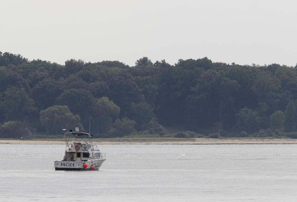 A police boat is stationed near the opening to the Long Island Sound in Lloyd Harbor, N.Y., Thursday, July 5, 2012.  Police say three bodies have been pulled out of New York's Long Island Sound after a yacht capsized on the Fourth of July and 24 others were rescued. (AP Photo/Seth Wenig)