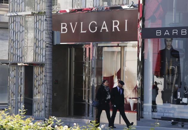Tourists walk past the Bulgari boutique on Rodeo Drive, decorated for Christmas, in Beverly Hills