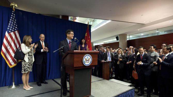 U.S. Ambassador to China Gary Locke delivers his speech on stage, as his wife Mona, right, California Gov. Jerry Brown, second from left, and his wife Anne Brown, left, and invited guests applaud during a Trade and Investment reception at the U.S. Embassy in Beijing Wednesday, April 10, 2013. (AP Photo/Andy Wong, Pool)