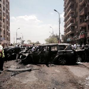 Security forces and emergency personnel inspect damages…