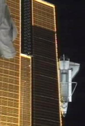 A photo made from NASA television shows the Atlantis as it passes under a solar panel on the Internatoinal Space Station after undocking Tuesday July 19, 2011,   Atlantis is the last Space Shuttle that will go to the International Space Station.  (AP Photo/NASA)