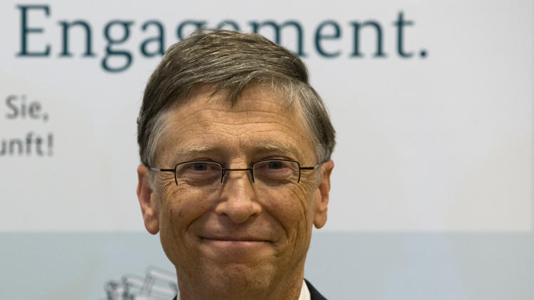 Bill Gates, founder of the software company Microsoft, poses for the media prior to a press conference after a meeting with German Development Aid Minster Dirk Niebel, unseen, in Berlin, Germany, Tuesday, Jan. 29, 2013. Slogan in the background reads 'Commitment'. (AP Photo/Michael Sohn)