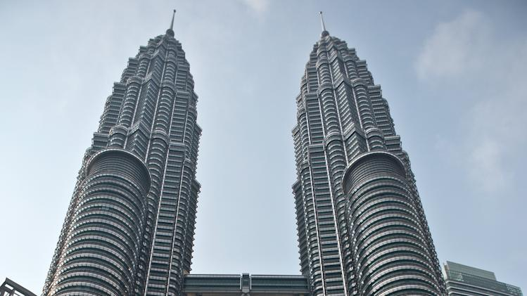 Tourists take photos at the Petronas Twin Towers in Kuala Lumpur on July 23, 2014