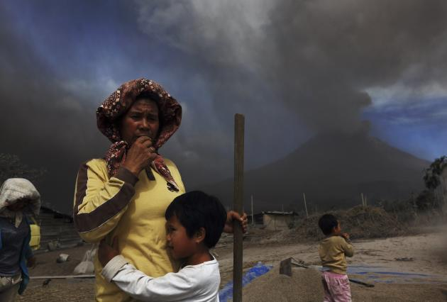 A child holds her mother as ash and smoke fill the air during an eruption in Mount Sinabung, at Tiga Pancur