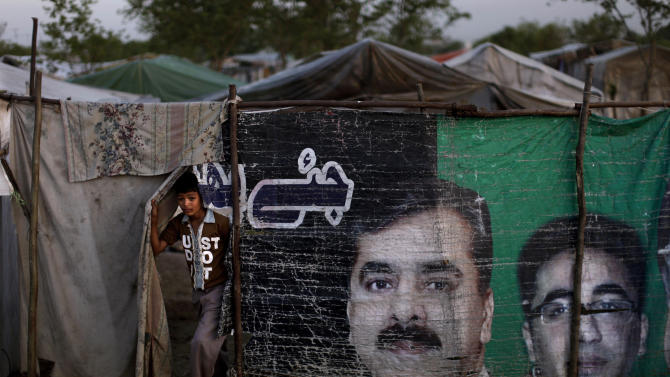 A Pakistani youth walks out his family's tent through a makeshift curtain showing pictures of ousted Prime Minister Yusuf Raza Gilani and Bilawal Bhutto Zardari, right, both from Pakistan People's Party, PPP, in a Christian slum on the outskirts of Islamabad, Pakistan, Friday, April 5, 2013. Pakistani officials have provoked both laughter and criticism in recent days as they vetted potential candidates in the country's upcoming national elections with questions that veered between the controversial and the bizarre. (AP Photo/Muhammed Muheisen)