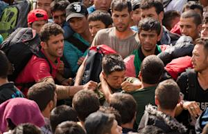 Migrants scuffle  as they queue up for buses after…