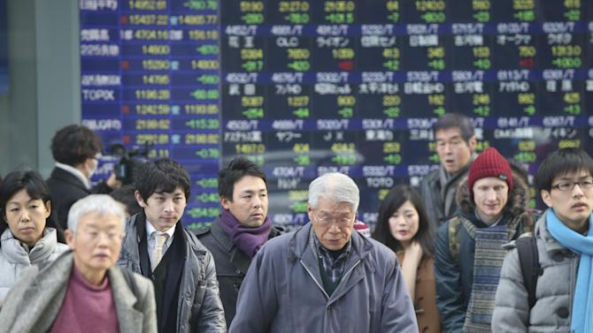 People walk by an electronic stock board of a securities firm in Tokyo, Friday, Feb. 12, 2016. Japan's main stock index dived Friday, leading other Asian markets lower, after a sell-off in banking shares roiled investors in the U.S. and Europe. (AP Photo/Koji Sasahara)