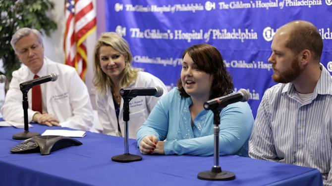 Dr. Scott Adzick, left, and Dr. Holly L. Hedrick, look on as Shellie and Greg Tucker, parents of Allison, and Amelia,  nine-month-old girls who were formerly conjoined twins, speak during a news conference at Children's Hospital of Philadelphia (CHOP) Thursday, Dec. 20, 2012, in Philadelphia. Surgeons at CHOP separated the Tucker girls during a seven-hour operation in November. The infants from Adams, N.Y., had been joined at the lower chest and abdomen. They shared their chest wall, diaphragm, pericardium and liver. (AP Photo/Matt Rourke)