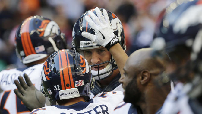 Denver Broncos' Peyton Manning, center, celebrates with teammates after he threw a touchdown pass against the Houston Texans during the third quarter of an NFL football game on Sunday, Dec. 22, 2013, in Houston. The touchdown pass was his 51st of the season. (AP Photo/David J. Phillip)