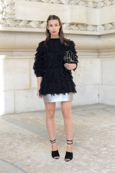 Balance out the raciness of a silver leather mini skirt with a cozy, shaggy black sweater. Minimalist strappy black sandals and feminine, half-up hair add the finishing touch. (Kristin Sinclair/Getty)