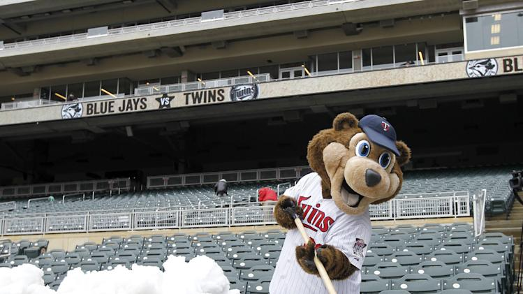 Minnesota Twins mascot T.C. shovels snow off the top of the Twins dugout and into the television camera pit before the first baseball game of a doubleheader against the Toronto Blue Jays in Minneapolis, Thursday, April 17, 2014.  Wednesday night's game was rescheduled for Thursday night due to a winter storm in Minnesota