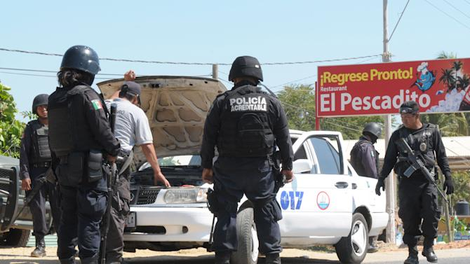 State police check a taxi at a roadblock due to stepped up security after masked armed men broke into a beach home, raping six Spanish tourists who had rented the house in Acapulco, Mexico, Tuesday Feb. 5, 2013. According to the mayor of Acapulco, five masked men burst into a house the Spaniards had rented on the outskirts of Acapulco, in a low-key area near the beach, and held a group of six Spanish men and one Mexican woman at gunpoint, while they raped the Spanish women before dawn on Monday. (AP Photo/Bernandino Hernandez)