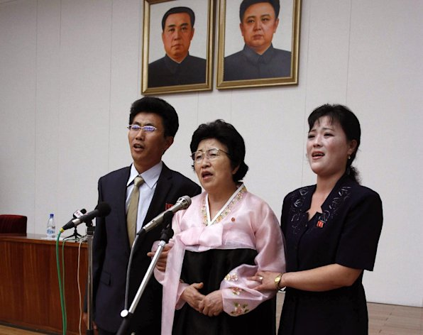 North Korean Pak Jong Suk, center, sings a Korean song titled My Unforgettable Path with her son and daughter-in-law while standing under portraits of former North Korean leaders Kim Il Sung, left, and Kim Jong Il after speaking to reporters at the Peoples Palace of Culture in Pyongyang, North Korea, on Thursday, June 28, 2012. Pak told local and foreign reporters she was tricked into defecting to South Korea by agents who offered to arrange a reunion with her long-lost father, but returned home after being disillusioned with life in the South. Her account could not be verified by South Korean officials. (AP Photo/Kim Kwang Hyon)