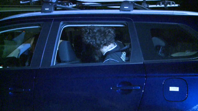 Still image of a man detained by police during a raid sitting in a car in Sydney