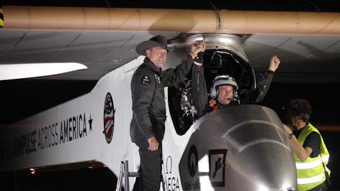 Solar Impulse co-founder, pilot and CEO Andre Borschberg, left, greets pilot Bertrand Piccard at Sky Harbor International Airport in Phoenix, early Saturday, May 4, 2013, after completing the first leg of its coast-to-coast flights across the United States. It is the first time that a solar airplane capable of flying day and night without fuel, will attempt to fly across America. Solar Impulse began its journey Friday in San Francisco in its attempt to reach New York. (AP Photo/Scuteri)