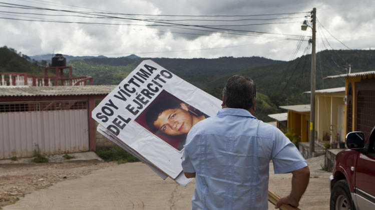 "In this Oct. 18, 2012 photo, Wilfredo Yanez carries a sign with an image of his late son Jaasiel Yanez that reads in Spanish ""I'm a victim of the army,"" in Tegucigalpa, Honduras. According to his relatives, Jaasiel was killed by soldiers early Sunday, May 27, when he was riding a motorcycle, near a military checkpoint, allegedly accompanied by a young woman.  (AP Photo/Esteban Felix)"