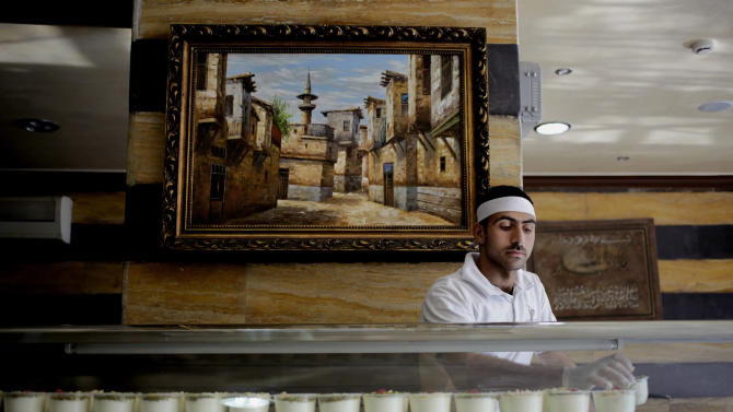 Syrian refugee worker, Mohammed Ali, 25, from Yalda, Damascus, organizes ice cream cups, at the Bakdash ice cream store, in Amman, Jordan, Wednesday, June 19, 2013. For Syrians, no visit to Damascus' Old City is complete without a stop at a more than century-old ice cream parlor in its main souq where you can watch them make their distinctive desert by pounding it into shape with giant wooden mallets, then enjoy a bowl of it sprinkled with pistachios. A painting of a neighborhood in Old Damascus is seen at background. (AP Photo/Mohammad Hannon)