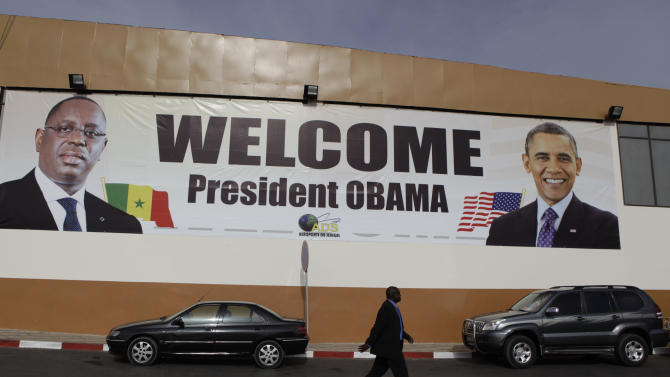 A banner showing U.S. President Barack Obama and Senegalese counterpart Macky Sall hangs at the airport in Dakar, Senegal, Wednesday, June 26, 2013. President Obama opened a weeklong trip to Africa on Wednesday, a three-country visit aimed at overcoming disappointment on the continent over the first black U.S. president's lack of personal engagement during his first term. (AP Photo/Rebecca Blackwell)