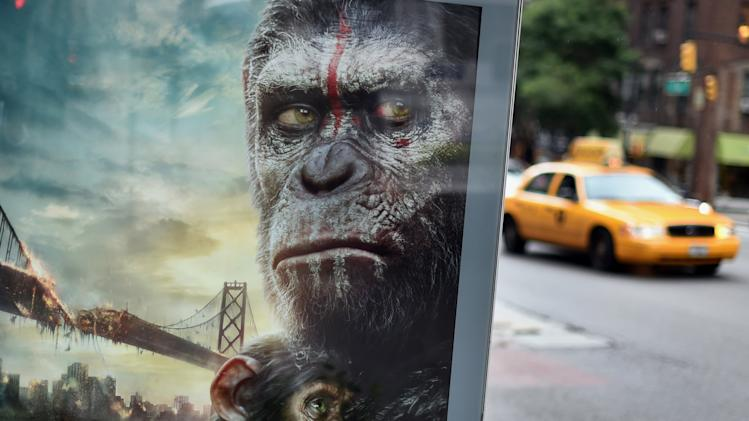 "A New York City taxi passes by a movie poster on a bus stop of ""Dawn of the Planet of the Apes"" on July 14,2014"