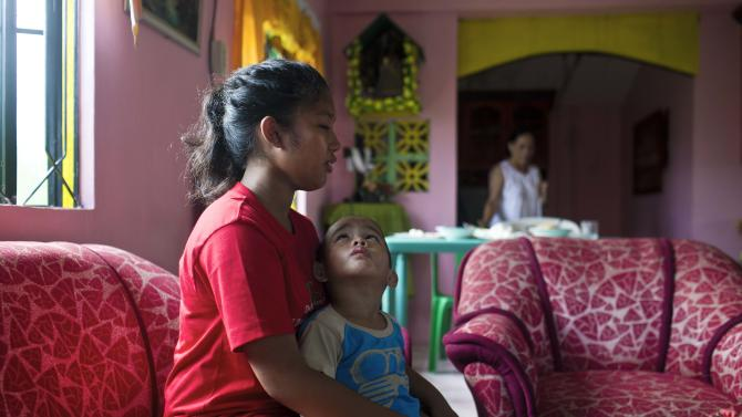 In this Nov. 21, 2013 photo, Shylyny Therese Negru, 15, holds her youngest brother, Rainier Aaron Dacuno, 3, as they sit in a relative's home in the town of Burauen, the Philippines. The children are among an unknown number of children in the eastern Philippines who lost their parents to the massive Nov. 8 storm. (AP Photo/David Guttenfelder)