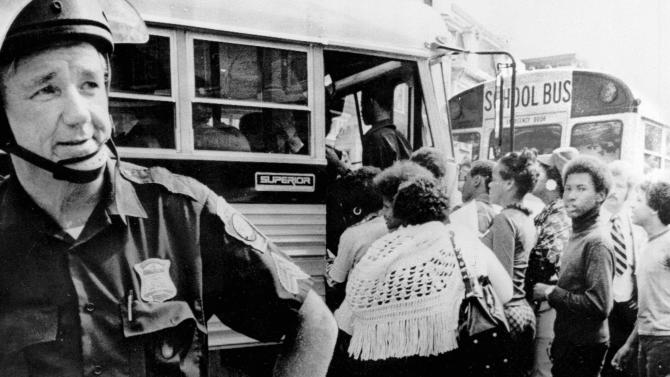 In this 1974 file photo, police guard while black students board a school bus as Boston begins a school busing program. The nonprofit Union of Minority Neighborhoods is hosting a group of exercises across Boston in 2013, where participants talk about how the city's busing crisis impacted them in the 1970s. Organizers hope it will unite people to fight for better access to quality public schools for all students, even as another new Boston school assignment system starts. (AP Photo/Peter Bregg, File)