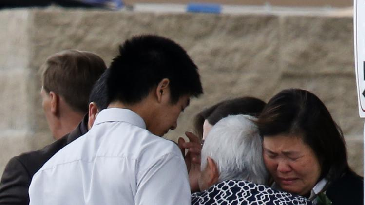 Family and friends hug after the funeral of Lawrence Hong in Calgary.