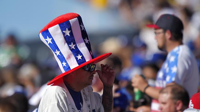 Los Angeles Dodgers fan Carlos Matallana, left, wearing a U.S. flag-inspired hat, walks through the crowd during a baseball game between the Dodgers and the New York Mets, Saturday, July 4, 2015, in Los Angeles. (AP Photo/Mark J. Terrill)