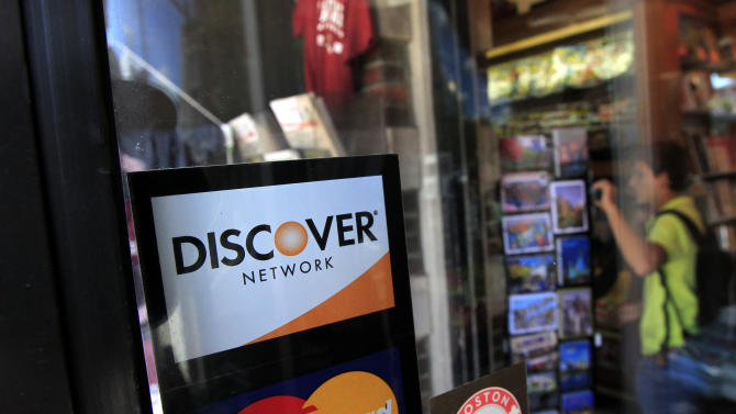 FILE - In this Monday, Sept. 24, 2012, file photo, a Discover logo is adhered to a window at the entrance of a shop in Cambridge, Mass. Discover Financial Services on Thursday, Dec. 20, 2012 reported higher earnings for its fiscal fourth quarter, as users of its namesake credit card stepped up purchases and the company wrote off fewer unpaid balances. (AP Photo/Steven Senne, File)