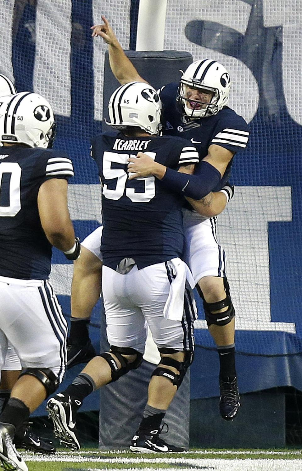 Brigham Young quarterback Taysom Hill (4)celebrates with teammate Brayden Kearsley (55) in the first quarter during an NCAA college football game against Texas, Saturday, Sept. 7, 2013, in Provo, Utah. (AP Photo/Rick Bowmer)