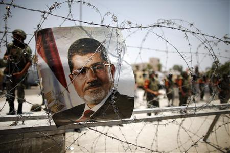 A portrait of deposed Egyptian President Mohamed Mursi is seen on barbed wire outside the Republican Guard headquarters in Cairo in this July 6, 2013 file photo. REUTERS/Khaled Abdullah/Files