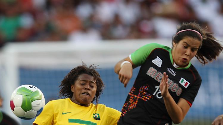 Brazil's Andreia Santos, left, fights for the ball with Mexico's Tanya Samarzich during a women's soccer semifinal match at the Pan American Games in Guadalajara, Mexico, Tuesday, Oct. 25, 2011. Brazil won 1-0.  (AP Photo/Juan Karita)